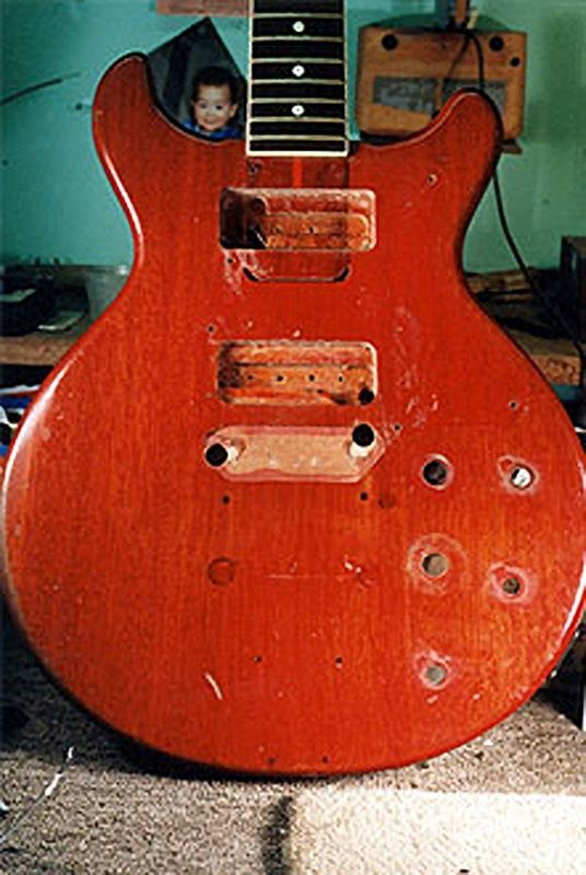 image of electric guitar that has holes on the top