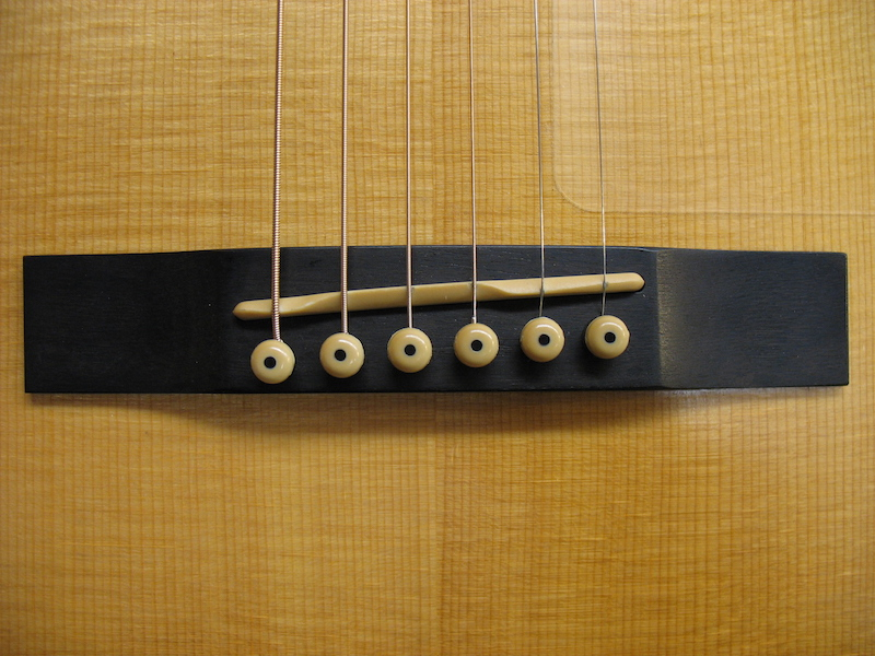 The original saddle, bridge, and strings placements of right-handed acoustic guitar